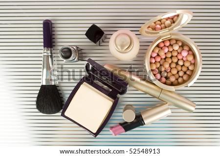 Cosmetics on the table. Basic colors pink and gold. Powder, skin cream, lipstick, handbag, vanity case, brush, eyeliner - stock photo