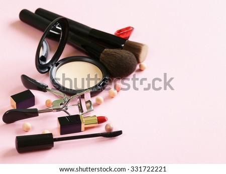 cosmetics set for make-up (face powder, lipstick, mascara brush) - stock photo