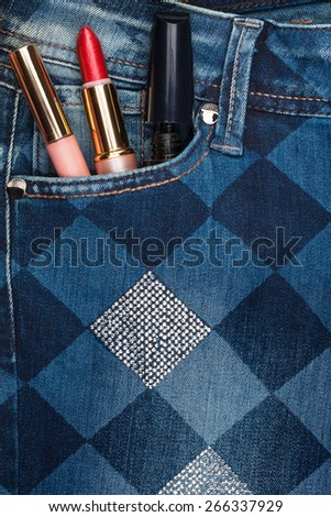 Cosmetics sticks out of the pocket of his jeans with rhinestones, as background - stock photo