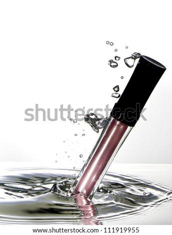 Cosmetics water splash pink nail polish - stock photo