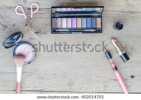 Cosmetics with eye shadow, eye liner, powder, lipstick,  and eyelash curler on wood table. Top view. - stock photo