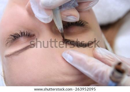 Cosmetologist applying permanent make up on eyebrows- eyebrow tattoo - stock photo