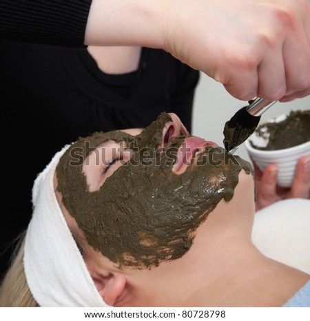 cosmetologist applying seaweed beauty mask at woman face - stock photo