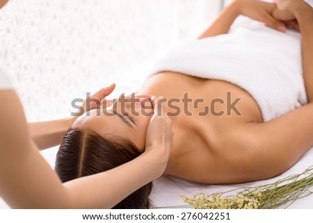 Cosmetologist massaging face on young woman - stock photo