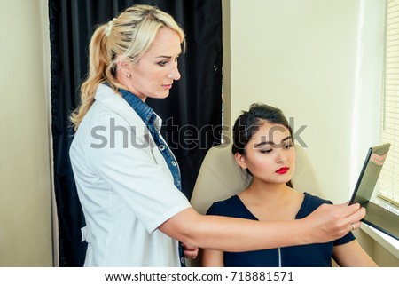 cosmetologist shows the customer something in the beauty salon.