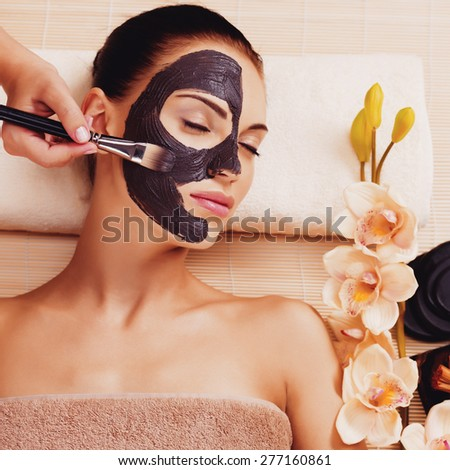 Cosmetologist smears cosmetic mask on the face of the woman in the sap salon - stock photo