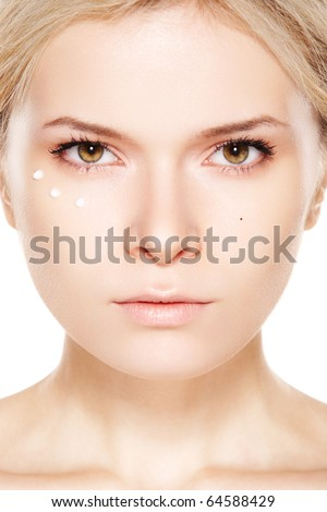 Cosmetology & cosmetic. Close-up portrait of beautiful woman which applying cream near eyes - stock photo