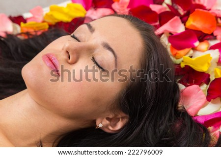 Cosmetology spa facial. Beautiful brunette in a spa salon. Girl lying on petals of roses in a beauty salon.?osmetology, beautician, beautiful background - concept of a facial care.  - stock photo