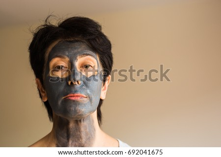 Cosmetology, spa, skin care and people concept - Woman applying Facial clay Mask. Beauty Treatments.