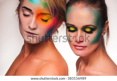 Cosmic beauty. Portrait of two beautiful women wearing artistic makeup posing with feathers white background - stock photo