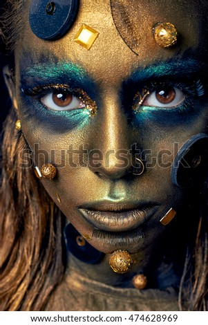 Cosmic unusual makeup with decorative elements on face, golden skin