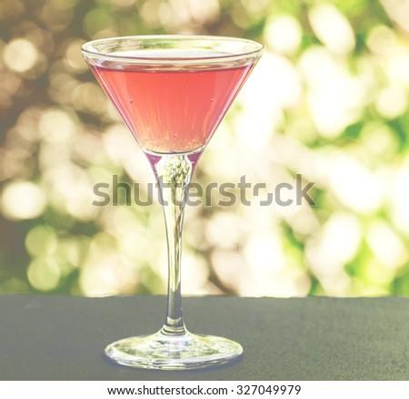 Cosmopolitan cocktail on a summer green nature bokeh background, selective focus - stock photo