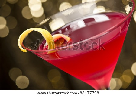 Cosmopolitan cocktail with lemon garnish in front of a gold glitter background - stock photo