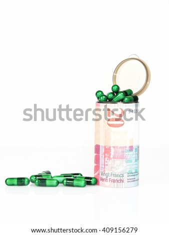 Cost of healthcare in Swiss Francs concept with green pharmaceutical capsules in and around a plastic container wrapped in a 20 Swiss franc banknote over white with copy space - stock photo