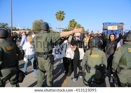 Costa Mesa, CA - April 28, 2016: Police in riot gear direct and control protesters of republican presidential candidate Donald Trump, at a rally at the Costa Mesa CA. - stock photo