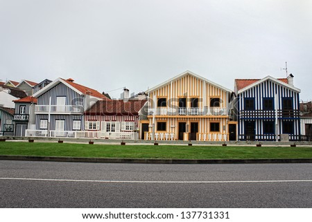 Costa Nova colorful striped houses in blue and yellow and red of the Beiras, Portugal, Europe under cloudy sky