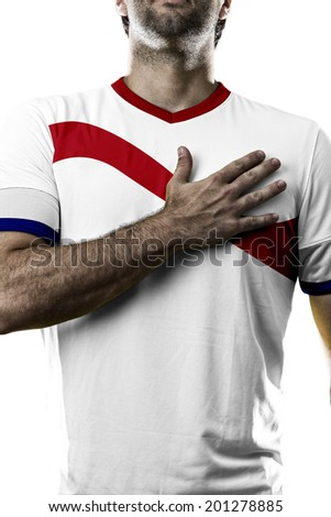 costa rican soccer player, listening to the national anthem with his hand on his chest. On a white background. - stock photo