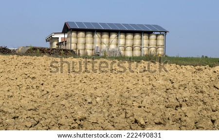 COSTA VESCOVATO, ITALY-OCTOBER 02, 2014: barn with solar panels on top roof, and agricultural plot, in Costa Vescovato. - stock photo
