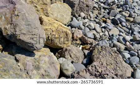 Costal sharp rocks and smooth pebbles found on Thornhill Broom Beach in La Jolla Canyon, Ventura county, California; nature background - stock photo