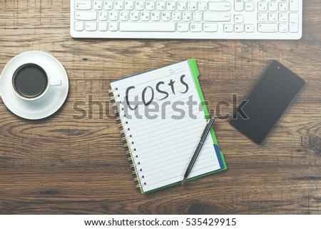 costs text on notebook on working table