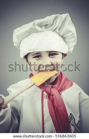 costume boy dressed as a cook with kitchen utensils - stock photo