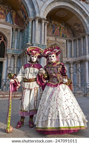 Costumed couple on the San Marco square during Carnival in Venice - stock photo