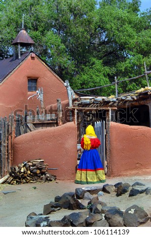 Costumed, female enactor enters rustic wooden courtyard of historic church at El Rancho De Las Golondrinas historic park in New Mexico.  Costume is bright red and yellow. - stock photo
