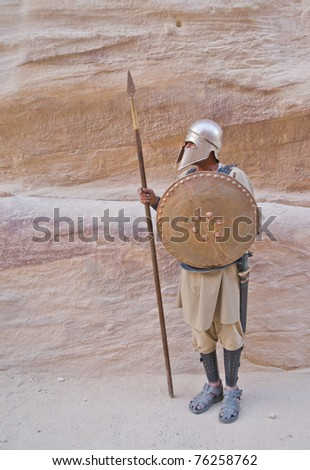 Costumed soldier guards ancient roadway through the Siq canyon into Petra, Jordan - stock photo