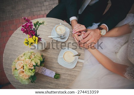 Cosy cafe wedding bouquet lying on the table. Bride and groom sitting at the table, having coffee and holding hands  - stock photo