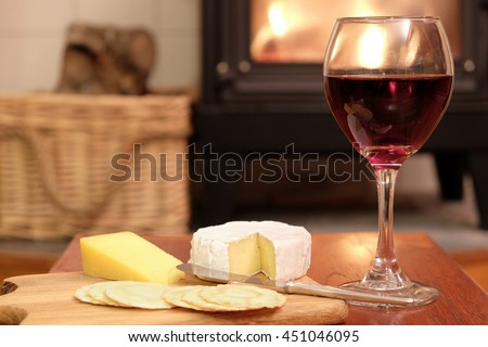 Cosy evening at home with red wine, brie or camembert cheese and crackers, in front of a fire in a woodburner or wood burning stove.