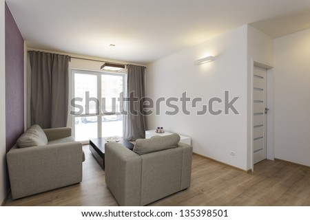 Cosy flat - bright living room with purple decoration on wall - stock photo