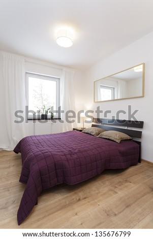 Cosy flat - huge purple bed in modern bedroom - stock photo