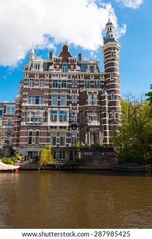 Cosy house on the bank of the Singelgrachtkering Canal. Amsterdam, the Netherlands. - stock photo