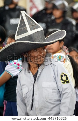 COTACACHI, ECUADOR - JUNE 25, 2016: Inti Raymi, the Quechua solstice celebration, with a history of violence in Cotacachi.  Mentally disabled man in parade costume stands in the road between groups.