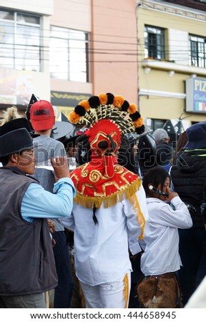COTACACHI, ECUADOR - JUNE 25, 2016: Inti Raymi, the Quechua solstice celebration, with a history of violence in Cotacachi. Man in a red devil mask dances in the square.