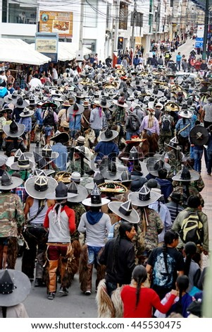 COTACACHI, ECUADOR - JUNE 29, 2106: Inti Raymi, the Quechua solstice celebration, with a history of violence in Cotacachi.  Overhead view of a community marching into town for the celebration.