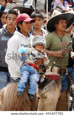 COTACACHI, ECUADOR - JUNE 29, 2016: Inti Raymi, the Quechua solstice celebration, with a history of violence in Cotacachi.  Man carries his young child in the dance circle.