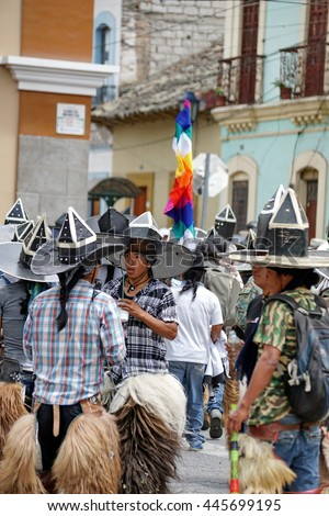 COTACACHI, ECUADOR - JUNE 29, 2016: Inti Raymi, the Quechua solstice celebration, with a history of violence in Cotacachi.  Community stomps and dances under the rainbow Quechua flag.
