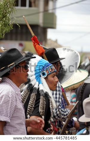 COTACACHI, ECUADOR - JUNE 29, 2016: Inti Raymi, the Quechua solstice celebration, with a history of violence in Cotacachi.  Man in an American Indian costume dances in the circle.