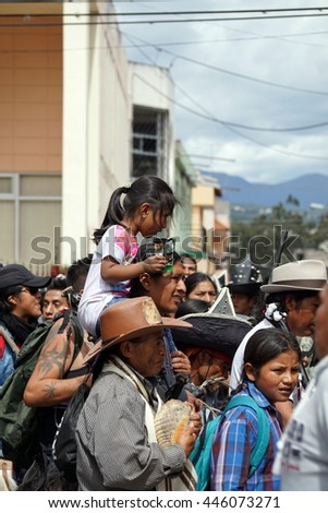 COTACACHI, ECUADOR - JUNE 29, 2016: Inti Raymi, the Quechua solstice celebration, with a history of violence in Cotacachi.  Man dances with his young daughter on his shoulders.
