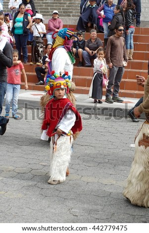 COTACACHI, ECUADOR - JUNE 23, 2016: Inti Raymi, the Quechua solstice festival, children's parade.  Boy in a devil mask and red poncho dances inside a circle by a man in a devil mask. - stock photo