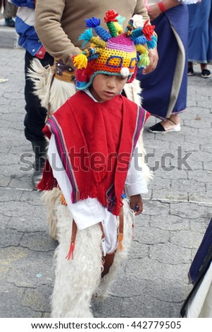 COTACACHI, ECUADOR - JUNE 23, 2016: Inti Raymi, the Quechua solstice festival, children's parade.  Boy in a devil mask and red poncho dances in a circle to wake up Mother Earth. - stock photo