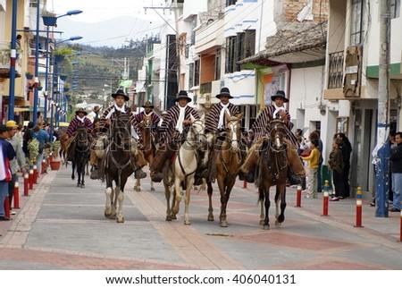 COTACACHI, ECUADOR - MAY 19, 2013: Group of men in ponchos in the Paseo de Chagras horse parade - stock photo
