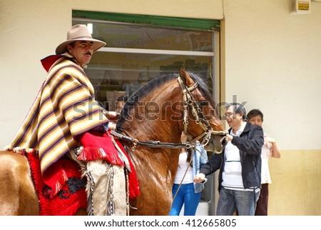 COTACACHI, ECUADOR - MAY 19, 2013: Man in a poncho on a horse in the Paseo de Chagra, or horse parade - stock photo