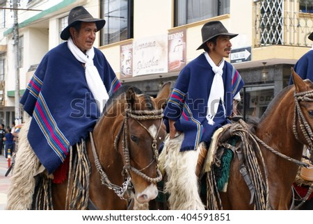 COTACACHI, ECUADOR - MAY 19, 2013: Men in blue ponchos on the back of horses in the Paseo de Chagra parade - stock photo