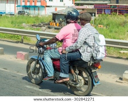 Cotonou, Benin: May 26: A man rides a hired Motorcycle taxi, the most common means of hired transportation in the city, on May 26, 2015 in Cotonou, Benin. - stock photo