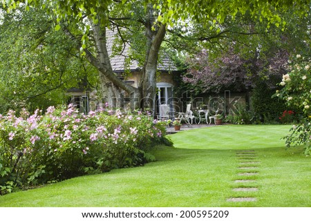 Cotswold Cottage Garden, with small patio outside and stoned path leading to it. - stock photo