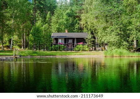 Cottage by the lake in rural Finland - stock photo