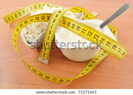 cottage cheese and yogurt with a centimeter tape on a wooden table