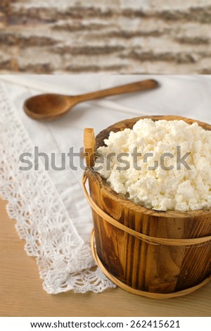 cottage cheese in a bowl on wooden table - stock photo